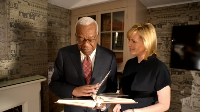 50th anniversary of news at ten; england: london: int sir trevor mcdonald and julie etchingham looking through photo album sir trevor mcdonald... - julie etchingham stock videos & royalty-free footage