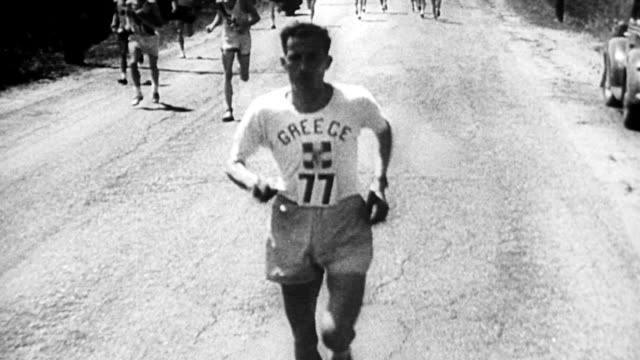 stockvideo's en b-roll-footage met 50th annual marathon race in boston / men running down rural road, suburbs of boston / spectators cheer runners on / stylianos kyriakides from... - 1946