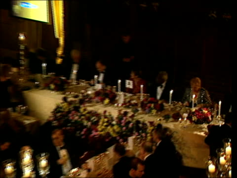 Sir Trevor McDonald sitting at banquet with others PULL OUT to i/c GV Video screen showing 'ITV50' logo PULL OUT