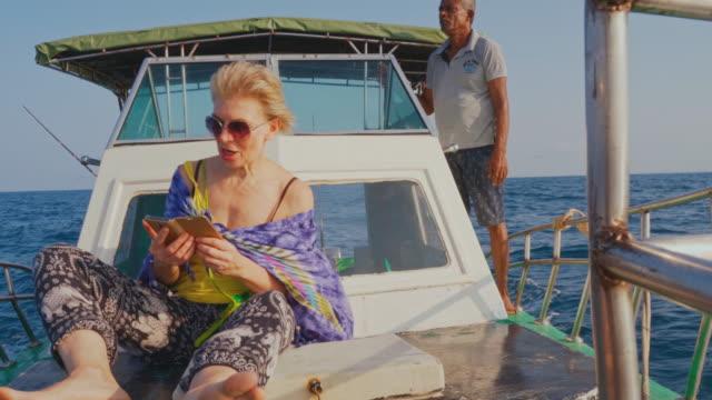 vídeos y material grabado en eventos de stock de una mujer europea activa y feliz europea de 50 años, una turista, descansa en la cubierta de un pequeño barco de pesca frente a la cubierta durante el viaje de pesca en alta mar en sri lanka. - 50 54 years