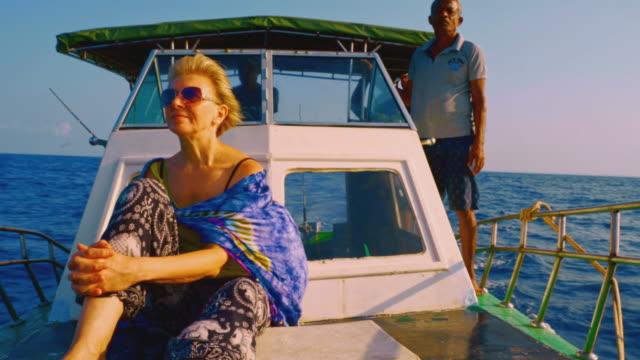 50歳の活発なヨーロッパのポジティブハッピーウーマン、観光客は、スリランカの深海釣り旅行中にデッキハウスの前で小さな漁船のデッキで休んでいます。 - 50 54 years点の映像素材/bロール