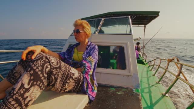 vídeos y material grabado en eventos de stock de una mujer europea activa de 50 años, una turista aburrida, descansa en la cubierta de un pequeño barco de pesca durante el viaje de pesca en alta mar cuando otro turista y un miembro de la tripulación descansan en la parte trasera del barco en el telón - 50 54 years