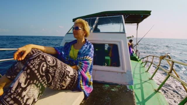 stockvideo's en b-roll-footage met een 50-jarige actieve europese vrouw, een verveelde toerist, rust op het dek van een kleine vissersboot tijdens de diepzeevisreis wanneer een andere toerist en een bemanningslid op de achterkant van het schip op de achtergrond rusten. - 50 54 years