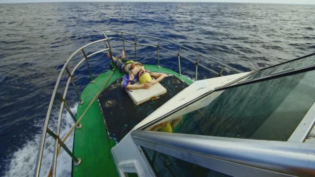 vídeos y material grabado en eventos de stock de una mujer europea activa de 50 años, una turista, se acuesta, descansa y toma el sol en la cubierta de un pequeño barco de pesca frente a la cubierta durante el viaje de pesca en alta mar en sri lanka. - 50 54 years