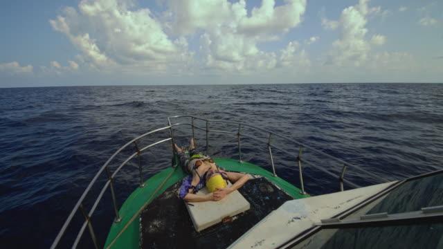 スリランカの深海釣り旅行中、観光客の50歳の活発なヨーロッパ人女性が、デッキハウスの前にある小さな漁船の甲板で横たわり、休息し、日光浴をしています。 - 50 54 years点の映像素材/bロール