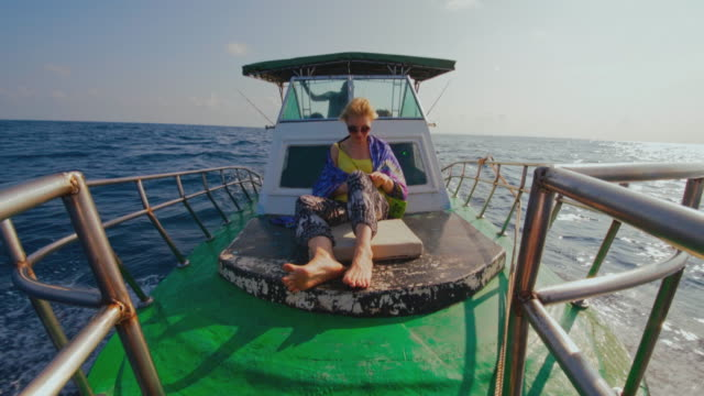 stockvideo's en b-roll-footage met een 50-jarige actieve europese vrouw, een toerist, rust en controleert haar smartphone op het dek van een kleine vissersboot tijdens de diepzeevisreis in sri lanka wanneer een kapitein het schip regeert vanuit een dekhuis op de achtergrond. - 50 54 years