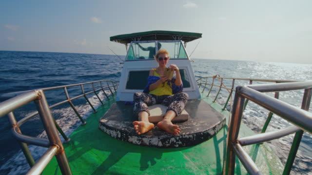 stockvideo's en b-roll-footage met een 50-jarige actieve europese vrouw, een toerist, rust op het dek van een kleine vissersboot en maakt foto's met een smartphone tijdens de diepzeevisreis in sri lanka wanneer een kapitein het schip regeert vanuit een dekhuis op de achtergrond. - 50 54 years