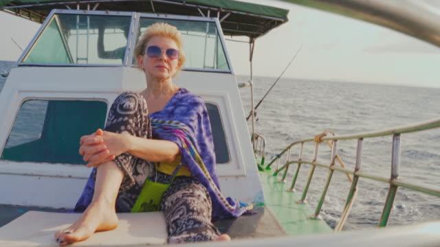 stockvideo's en b-roll-footage met een 50-jarige actieve europese vrouw, een toerist, rust op het dek van een kleine vissersboot tijdens de diepzeevisreis in sri lanka wanneer een kapitein het schip regeert vanuit een dekhuis op de achtergrond. - 50 54 years