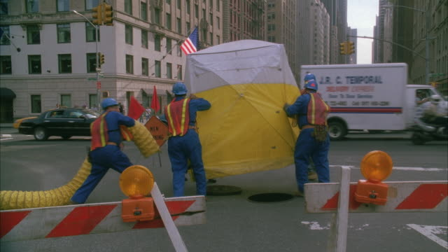 WS 59th Street And 6th Avenue intersection traffic, workers removing yellow tent revealing manhole / New York City, New York, USA