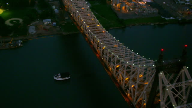 CLOSE UP AERIAL 59th Street Bridge from Roosevelt Island to Queens with boat passing under then PAN to Midtown Manhattan skyline at twilight