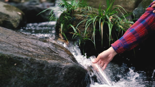 60p footage of a man gathering a water sample from a river - water conservation stock videos & royalty-free footage