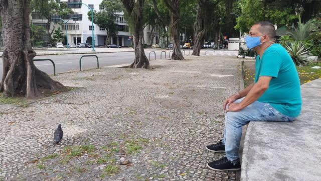 stockvideo's en b-roll-footage met 60-jarige man observeert beweging op straat tijdens pandemie - alleen één man
