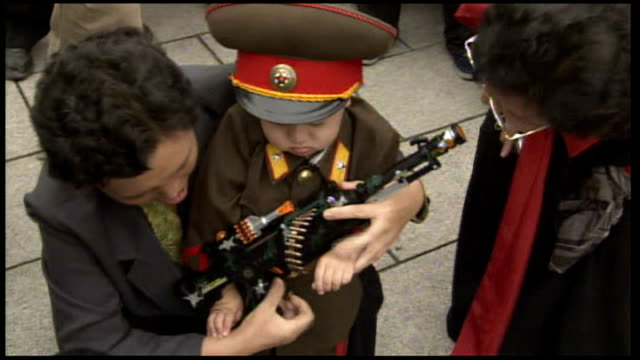 65th anniversary of communist rule celebrations NORTH KOREA Pyongyang EXT Small boy dressed as a North Korean General as his father helps him to hold...