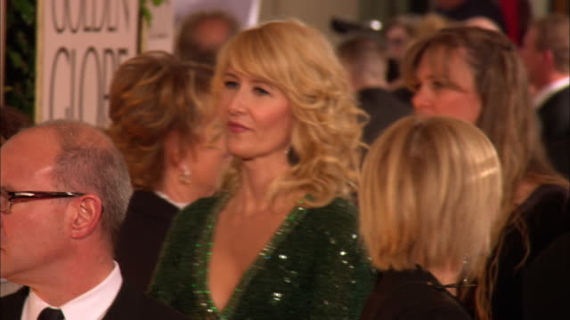 vídeos y material grabado en eventos de stock de 69th golden globe awards arrivals: hd: mcu laura dern moving through crowd with handler and talking with unidentified woman at the beverly hilton... - the beverly hilton hotel