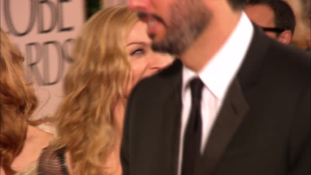 stockvideo's en b-roll-footage met 69th golden globe awards arrivals hd mcu/cu pan madonna smiling walking down the red carpet w/ handlers in crowd at the beverly hilton hotel - zanger
