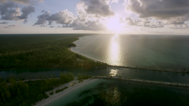 6k red aerial view of ocean and inlet at sunset - inlet stock videos and b-roll footage