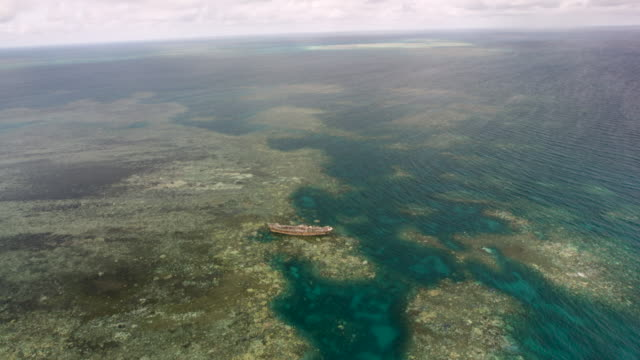 vídeos de stock, filmes e b-roll de 6k red ascending aerial view of double-barrier reef and shipwrecked boat - navio