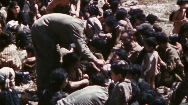 6th division marines helping civilians up a hill, tending their injuries, and giving them food / okinawa, japan - guerra del pacifico video stock e b–roll