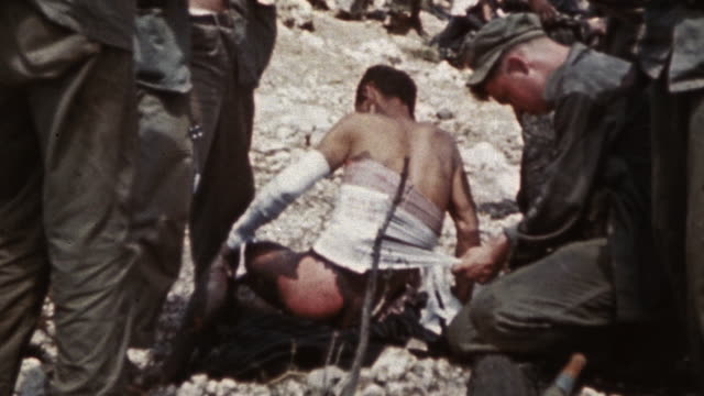 HA 6th Marine Division medic bandaging an injured prisoner of war with other marines watching / Okinawa Japan