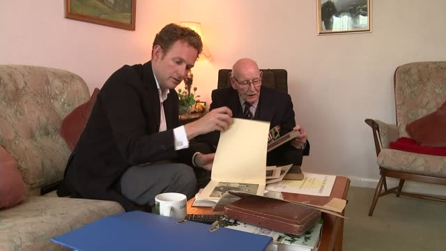 75th anniversary of dunkirk marked location unknown int capt alan gilbert and reporter looking at photographs - itvイブニングニュース点の映像素材/bロール