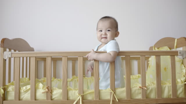 r/t ws 7-month baby girl playing and smiling on bed at home / chongqing, china - endast en flickbaby bildbanksvideor och videomaterial från bakom kulisserna