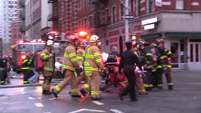 7pm dusk firefighters leaving east village building collapse patient on stretcher hook and ladder dousing building - 退院点の映像素材/bロール