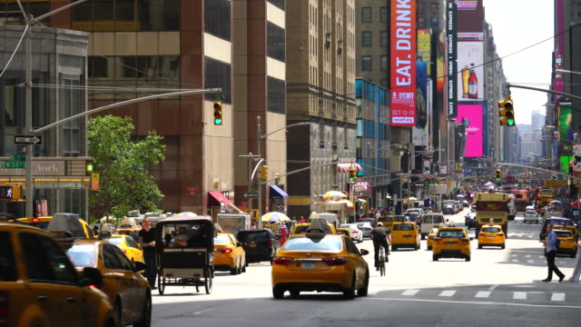 7th Avenue traffic goes through and pedestrians cross the Avenue among the rows of buildings at Midtown Manhattan New York City.
