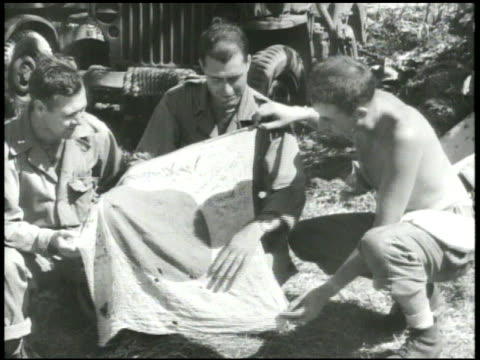 vídeos de stock, filmes e b-roll de s 7th marine division soldiers standing on top of hill w/ us flag flying vs soldiers looking at japanese flag questioning japanese prisoners of war... - crachá
