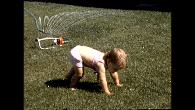 8mm home movie transfer of young female toddler wearing pink shirt on the green grass of a suburban lawn running and playing in a sprinkler in... - 園芸用散水機点の映像素材/bロール