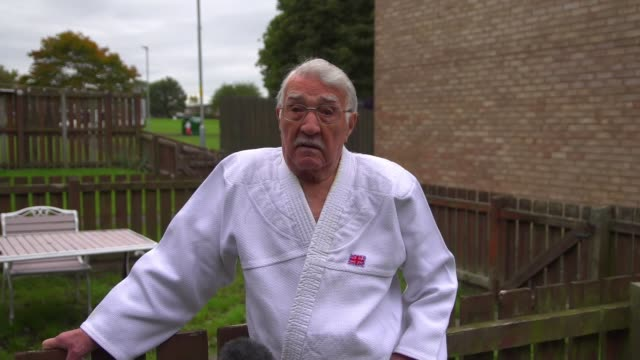 year-old man given judo's highest honour; england: northumberland: int jack hearn tying belt hearn hearn putting on flip flops tying red belt ext... - martial arts stock videos & royalty-free footage