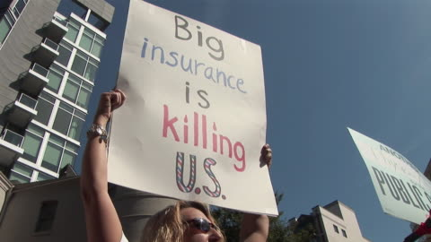stockvideo's en b-roll-footage met mar-2010 health care reform demonstration protest march to hotel where insurers were holding conference, nurse holding up placard / washington dc,... - 2010