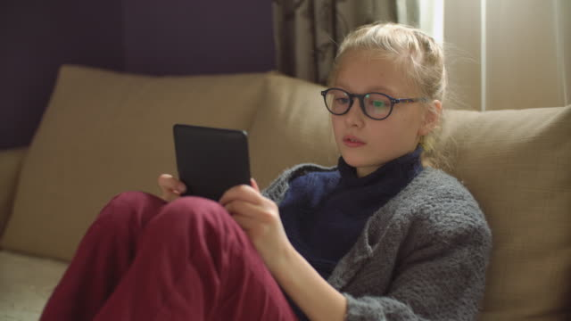 9-years girl reading e-book at home on the sofa - 8 9 years stock videos & royalty-free footage