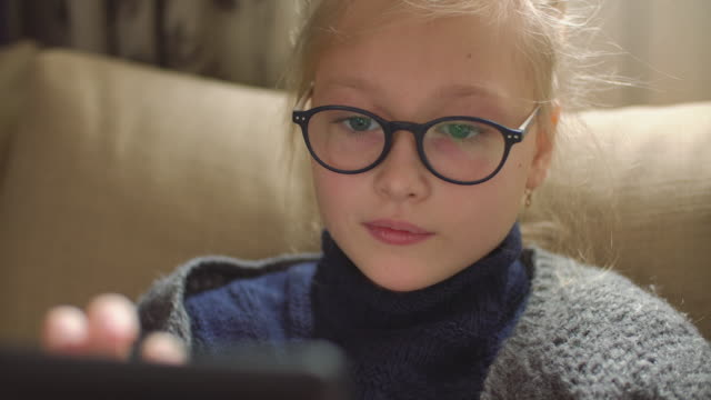 9-years girl reading e-book at home on the sofa - reading glasses stock videos & royalty-free footage