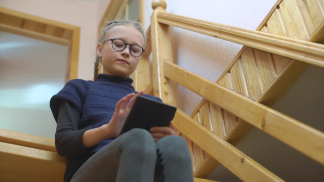 9-years girl reading e-book at home sitting on the stairs - 8 9 years stock videos & royalty-free footage