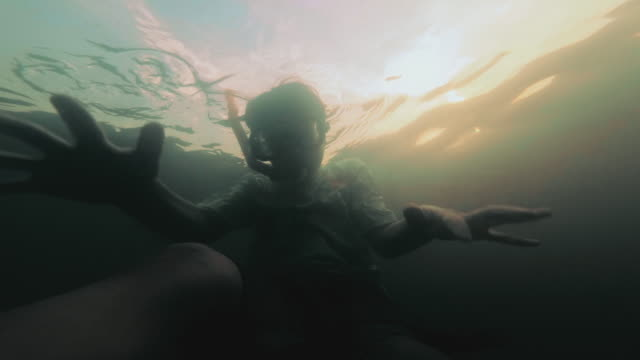 vídeos de stock e filmes b-roll de 9-years-old boy diving in a lake in the summer day. - pequeno lago