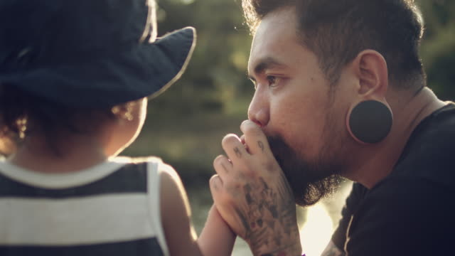 cu of a baby holds his father's hand while he kisses his hands. - tatuaggio video stock e b–roll