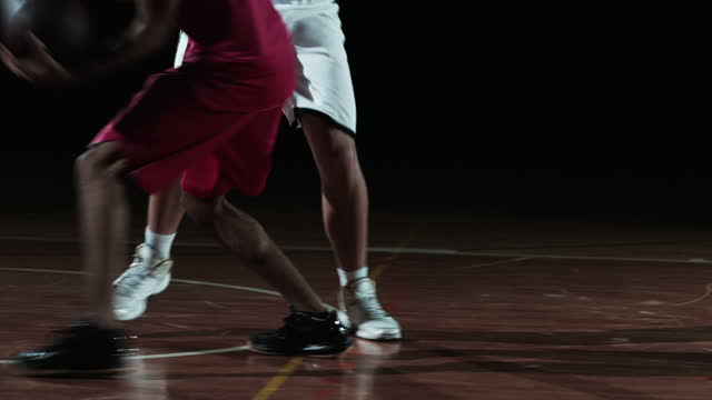 slo mo of a basketball player dribbling the ball against the opponent - basketball ball stock videos & royalty-free footage