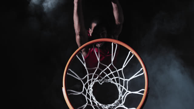 SLO MO of a basketball player in red performing slam dunk shot