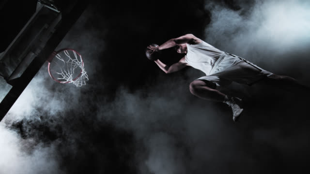 SLO MO of a basketball player performing a slam dunk