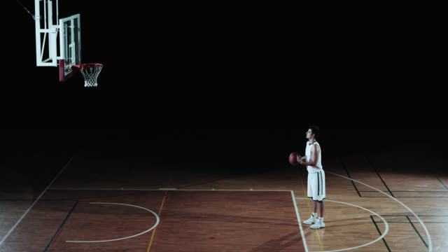 stockvideo's en b-roll-footage met slo mo of a basketball player shooting from a free throw line - studio shot