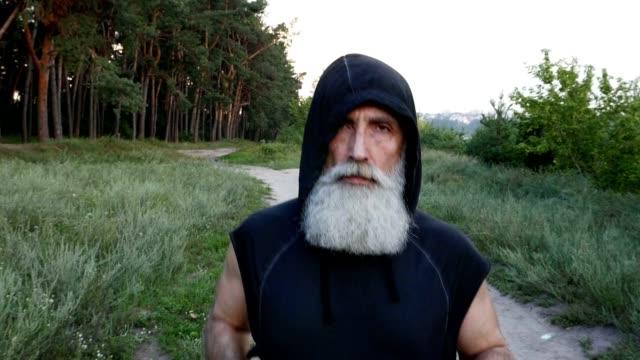 ein bärtiger alter mann läuft durch den wald. slow-motion - vollbart stock-videos und b-roll-filmmaterial
