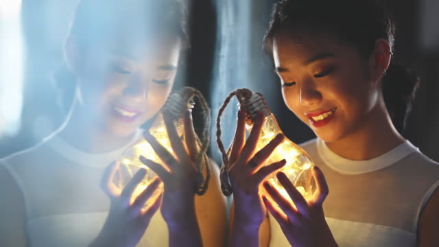 a beautiful asian chinese teenage girl looking and holding a light bulb with led light strings smiling with mirror reflection - malaysia stock videos & royalty-free footage