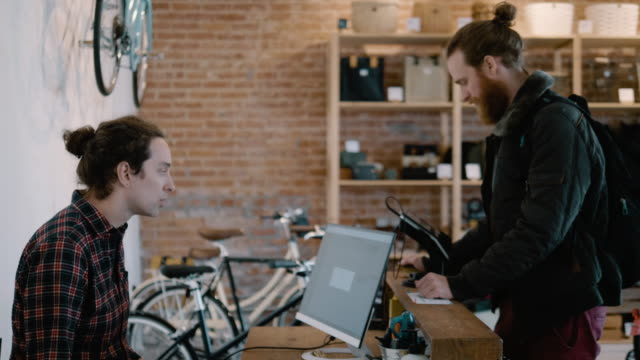 a bicycle shop owner begins a credit card transaction to sell a bicycle to a young man - partire bildbanksvideor och videomaterial från bakom kulisserna