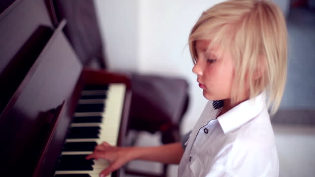 a blonde boy playing the piano