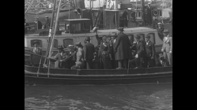VS a boat laden with people comes to a dock at a crowded harbor with exiled royalist Ioannis Metaxas on board waving his hat people on dock wave...