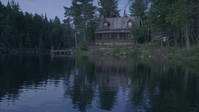 pov of a boat slowing drifting towards a cabin in the woods. - capanna di legno video stock e b–roll