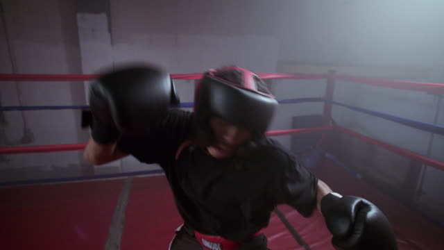 slo mo. pov of a boxer punching inside a boxing ring in a professional boxing gym - punching stock videos & royalty-free footage