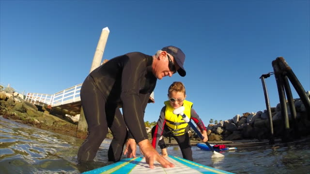 POV of a boy and his father paddling an SUP stand-up paddleboard in a marina.
