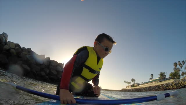 POV of a boy paddling an SUP stand-up paddleboard in a marina. - Slow Motion