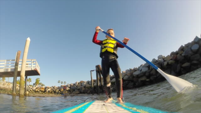 pov of a boy paddling an sup stand-up paddleboard in a marina. - slow motion - gente comune video stock e b–roll